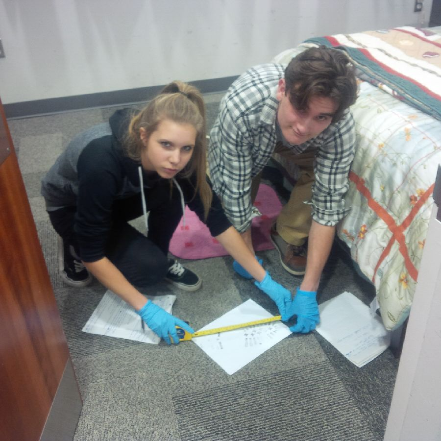 A female and male student wearing gloves crouch together measuring figures on a piece of paper using a tape measure.