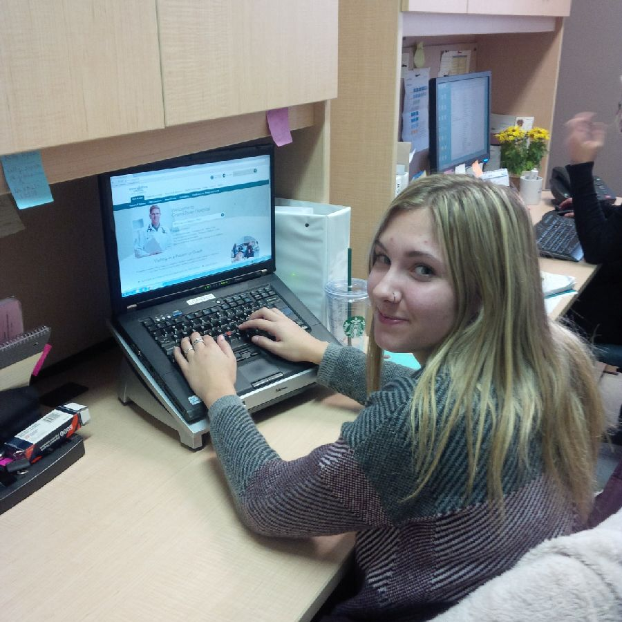 A smiling female student with blonde hair sits types on a laptop in an office setting.