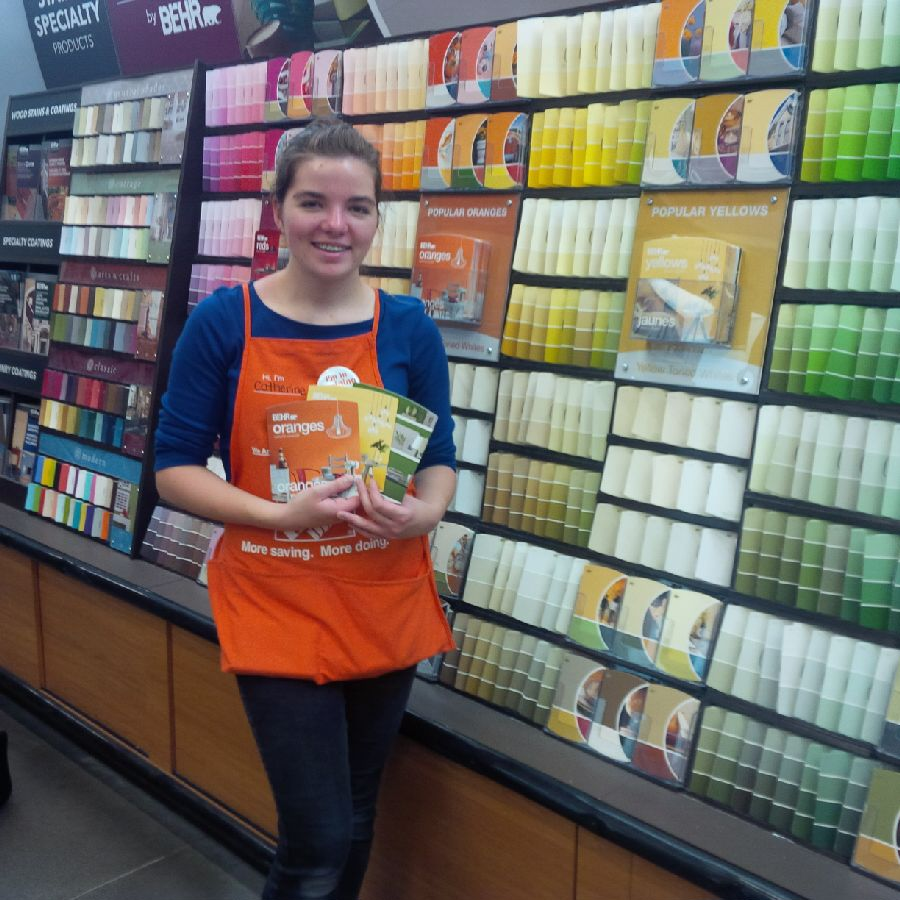 A female student in a Home Depot uniform holds up paint-related pamphlets standing next to shelves filled with paint sample cards.