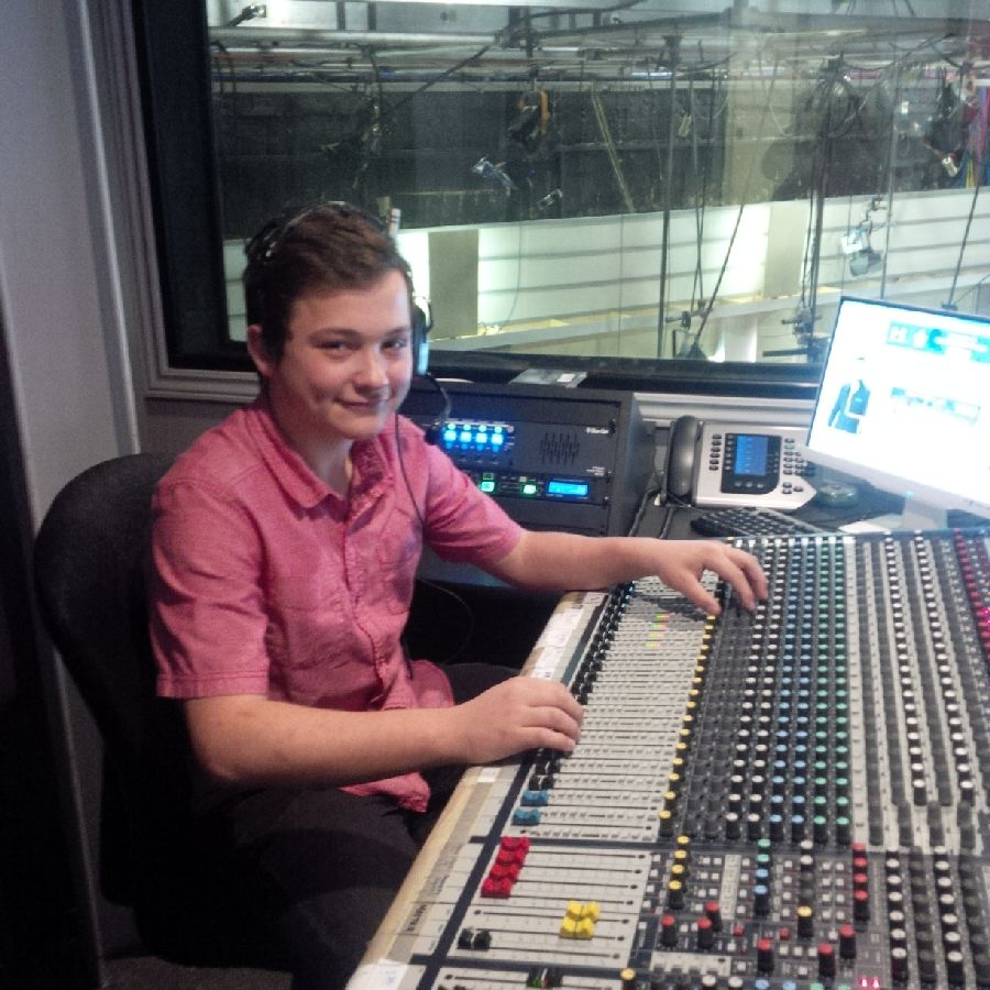 A smiling male student wearing a pink polo shirt sits before a mixing console at Rogers TV.