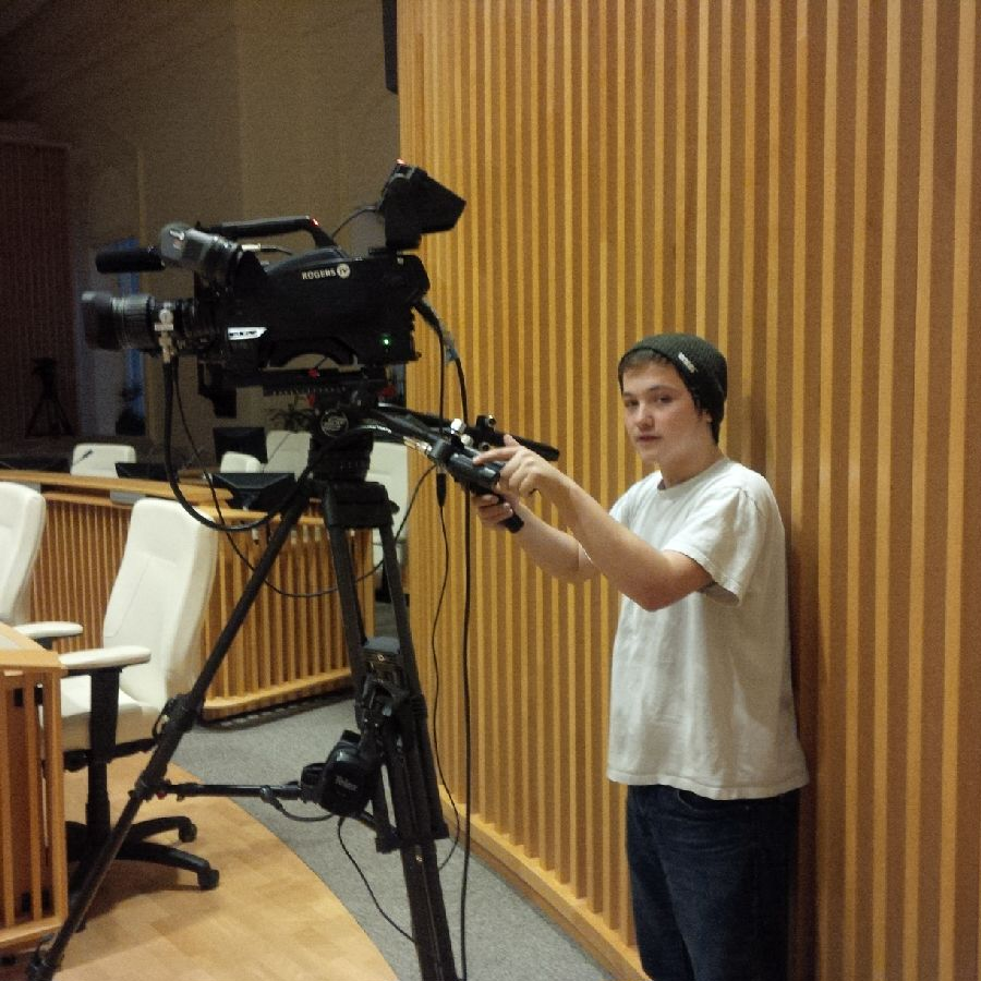 A male student wearing a white shirt handles a professional video camera for Rogers TV.