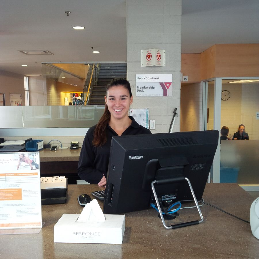 A female student wearing her dark hair in a ponytail smiles while working from behind the customer service counter at YCMA.